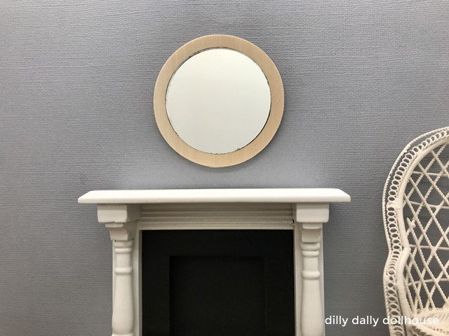 miniature wooden mirror frame above fireplace