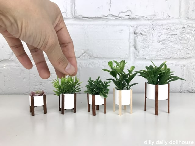 a line of modern miniature planters with hand visible
