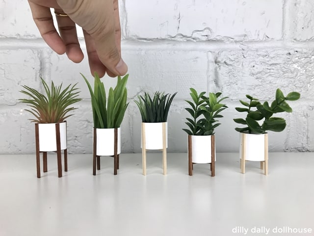 a line of DIY modern miniature planters with hand in scale