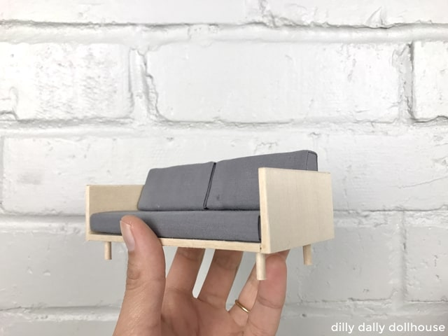 finished miniature wood case sofa held by hand