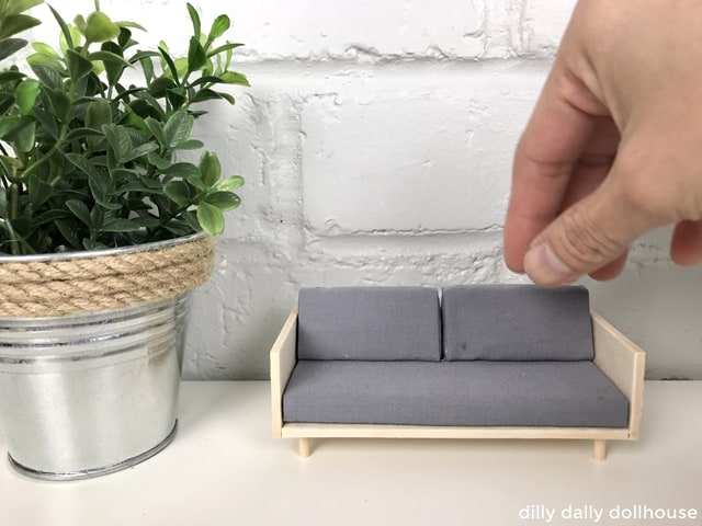 miniature wood case sofa held by hand
