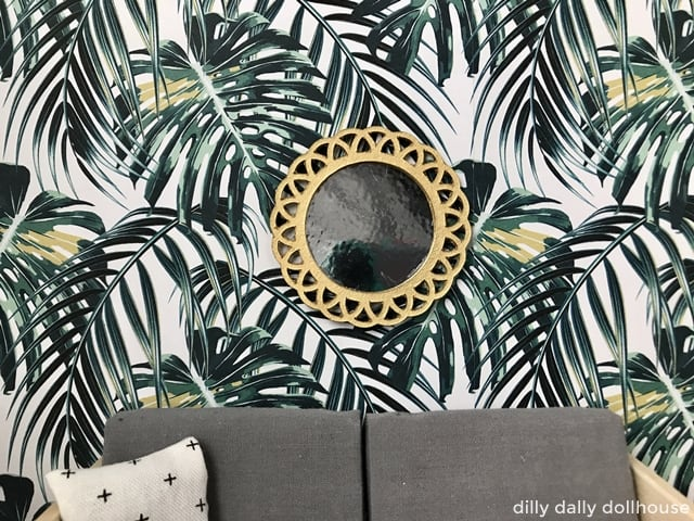 miniature dollhouse mirror above a sofa against planty wallpaper