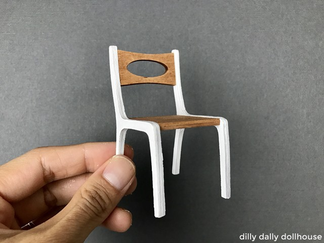 1:12 scale modern dollhouse dining chair held by hand